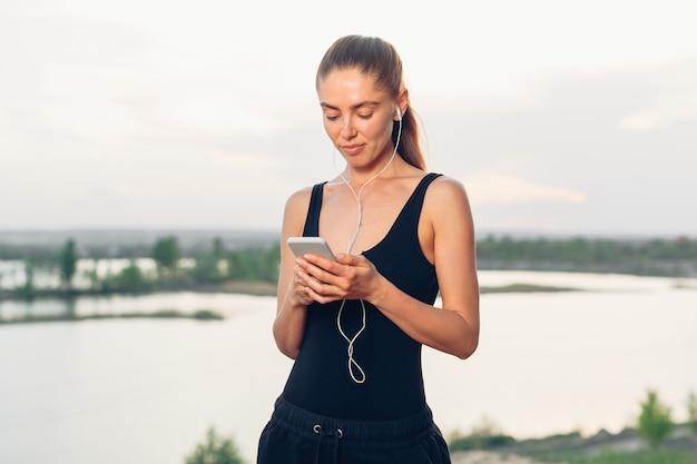 Mujer que escucha la aplicación de teléfono inteligente para música con equipo interno.