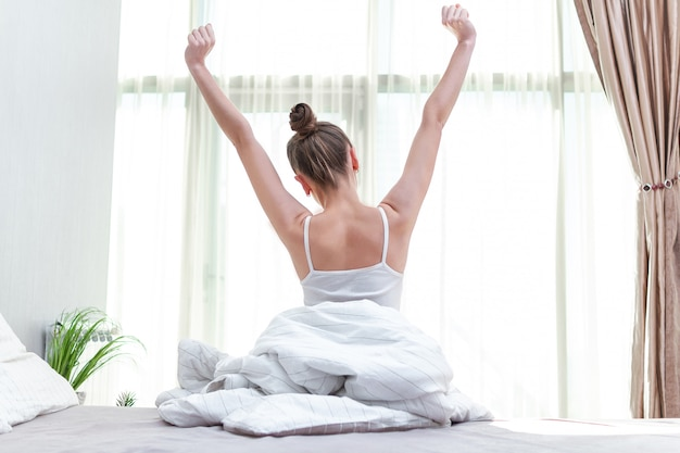 Mujer que se estira en la cama en casa e intenta levantarse temprano en la mañana para comenzar un nuevo día