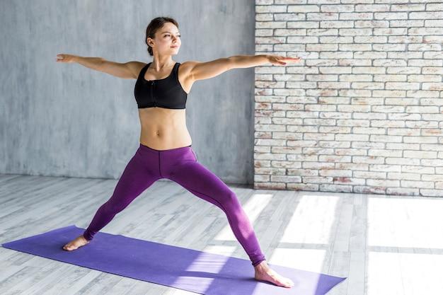 Mujer que se estira en una pose de yoga triángulo