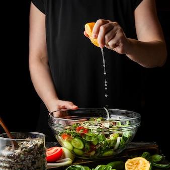 Mujer que exprime el limón en vista lateral de la ensalada gruesa.