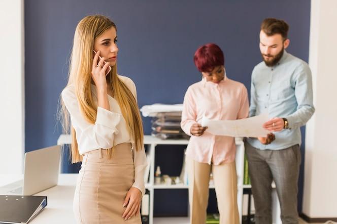Mujer que habla en el teléfono inteligente cerca de colegas que trabajan