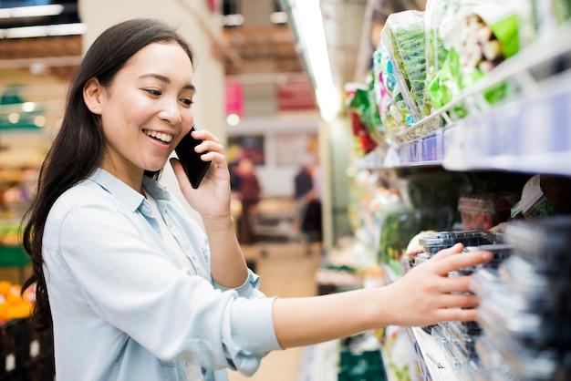 Mujer que habla en el teléfono inteligente en la tienda de comestibles