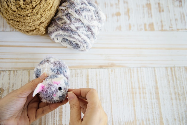Mujer que hace la muñeca de conejito encantadora de hilo - concepto de celebración de vacaciones de semana santa