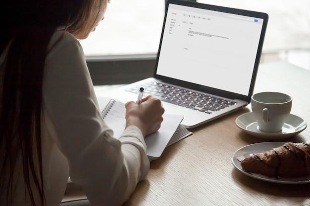 Mujer que hace notas que lee la letra del correo electrónico en el ordenador portátil en café