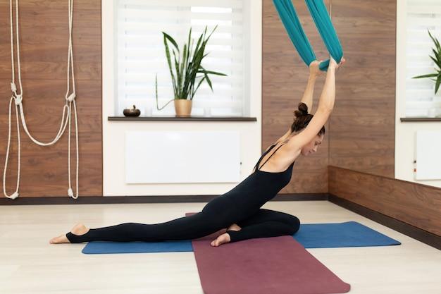 Mujer que hace la yoga de la mosca que estira ejercicios en gimnasio. estilo de vida en forma y bienestar