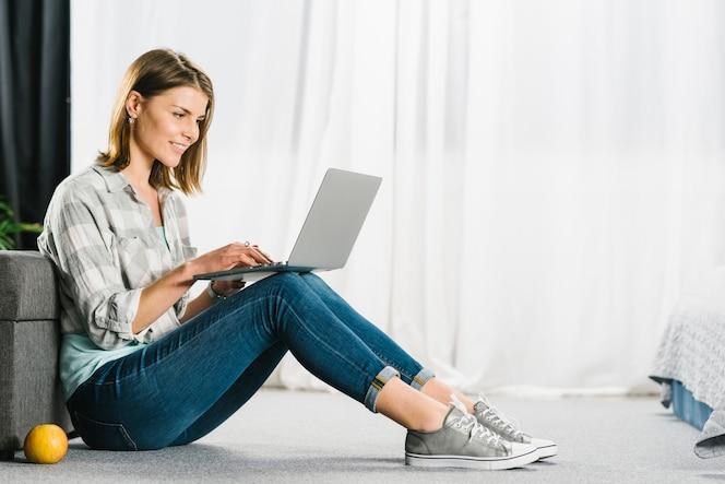 Mujer que hojea la computadora portátil en piso