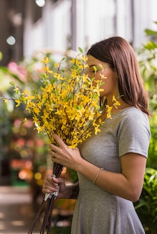 Mujer que huele flores amarillas
