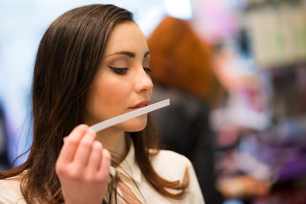 Mujer que huele un probador de perfume en una tienda