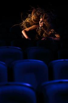La mujer que interpreta el papel de un fantasma o espíritu en el teatro está sentada entre las filas de sillas.