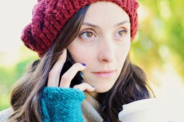 Mujer que invita al teléfono móvil y que sostiene una taza de café.