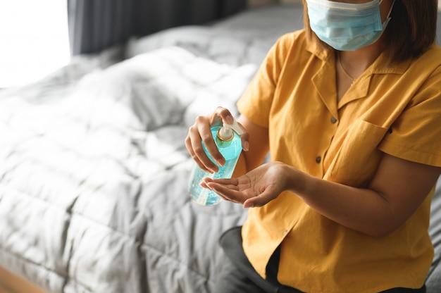 Mujer que se lava las manos con gel desinfectante de alcohol para proteger la infección del virus