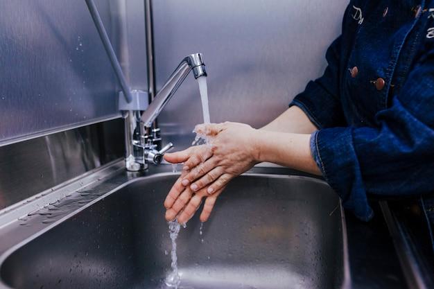 Mujer que se lava las manos en el negocio de panadería. interior