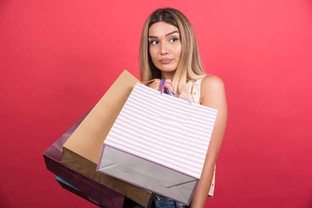 Mujer que lleva bolsas de la compra con expresión neutra en la pared roja.
