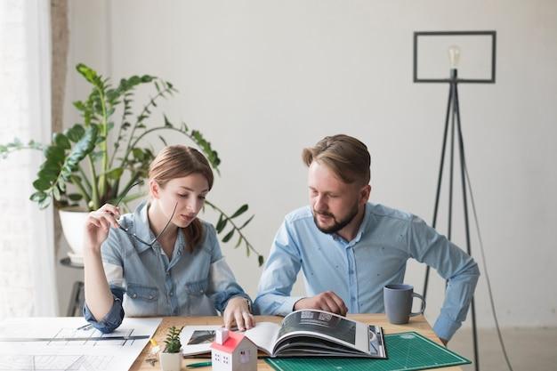Mujer que lleva a cabo el espectáculo que mira el catálogo interior con su compañero de trabajo masculino en la oficina