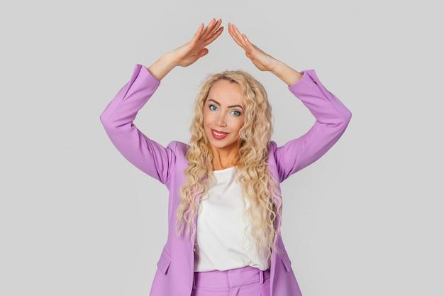 Mujer que lleva a cabo las manos arriba en el gesto del tejado de la casa, concepto del seguro.