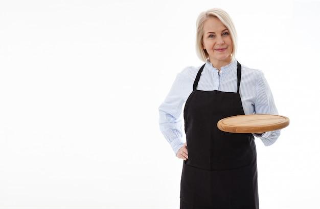 Mujer que lleva a cabo el tablero vacío de la pizza en la pared blanca.