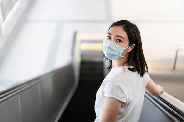 Mujer que lleva una máscara protectora de higiene para proteger el virus covid19 y la contaminación pm2.5 mientras viaja en un lugar lleno de gente. la mujer usa una mascarilla para proteger la crisis del virus corona en el país asiático. enfermedad