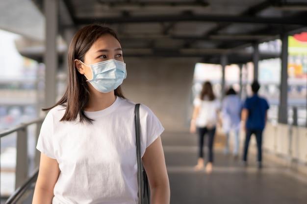 Mujer que lleva una máscara protectora de higiene para proteger el virus covid19 y la contaminación pm2.5 mientras viaja en un lugar lleno de gente.