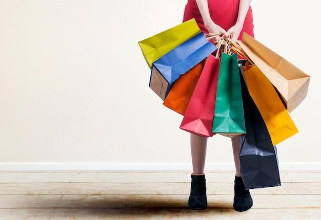 La mujer que llevaba bolsas de la compra de pie con pared blanca
