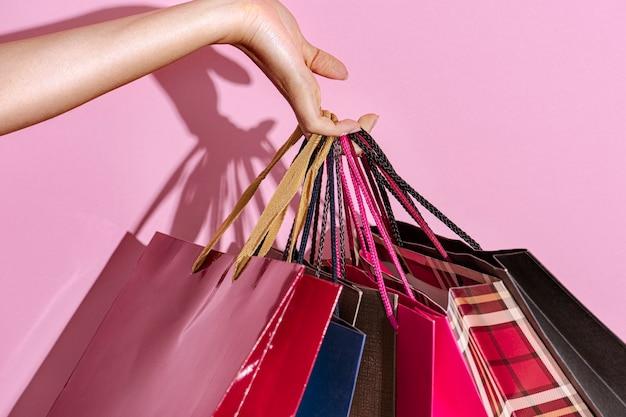 Mujer que llevaba bolsas de la compra sobre un fondo de color rosa