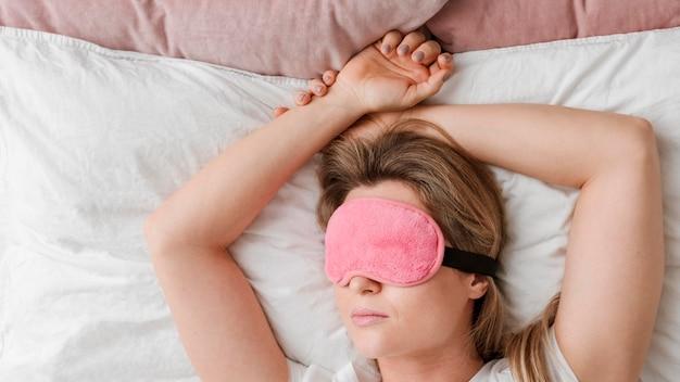 Mujer que llevaba una máscara para dormir en los ojos
