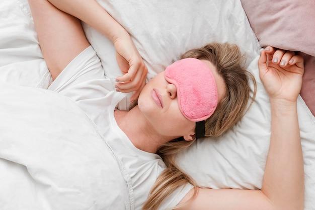 Mujer que llevaba una máscara para dormir en la vista superior de sus ojos