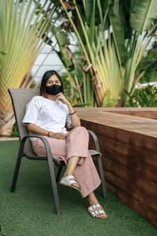 Mujer que llevaba una mascarilla sentado en una silla al lado de una piscina en el jardín.