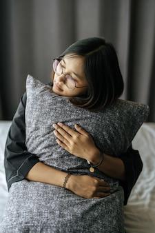 Mujer que llevaba una túnica negra, abrazando la almohada en la cama.