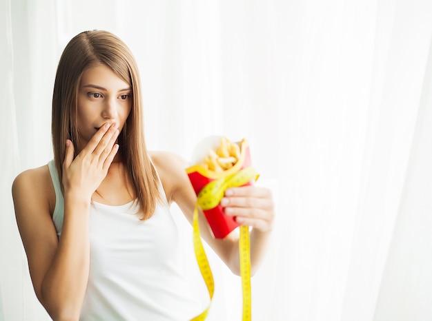 Mujer que mide el peso corporal en la balanza con comida chatarra poco saludable