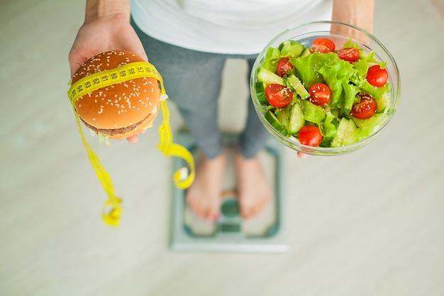 Mujer que mide el peso corporal en la balanza con hamburguesa y ensalada.