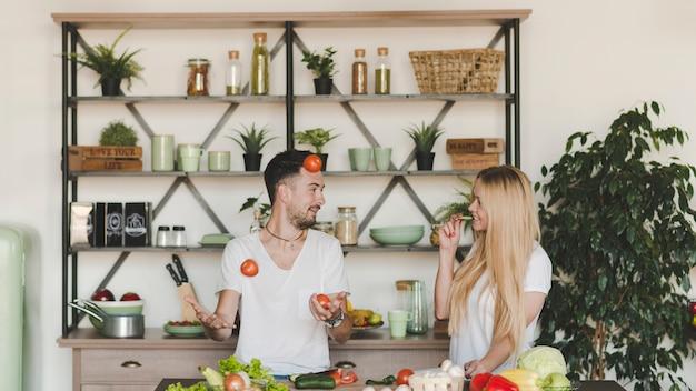 Mujer que mira al hombre que hace juegos malabares los tomates rojos en la cocina