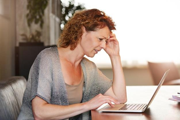 Mujer que mira el pensamiento de la computadora que se sienta en el vector