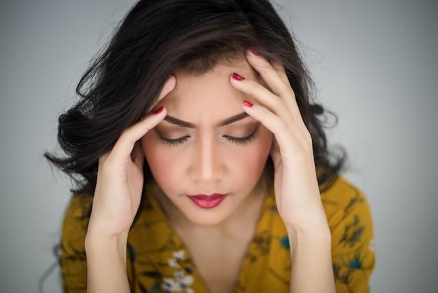 Mujer que muestra dolor de cabeza o estrés