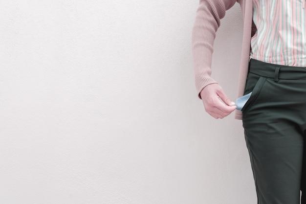 Mujer que muestra su bolsillo vacío en fondo de la pared.