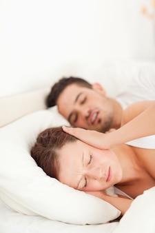 Mujer que no puede dormir debido a los ronquidos