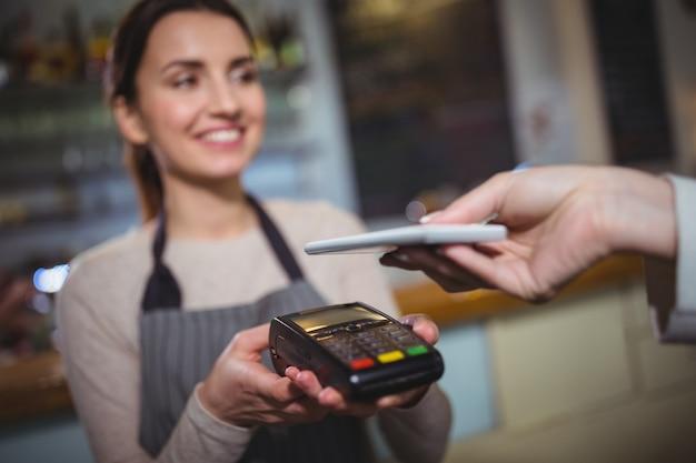 Mujer que paga la factura a través de teléfonos inteligentes usando la tecnología nfc