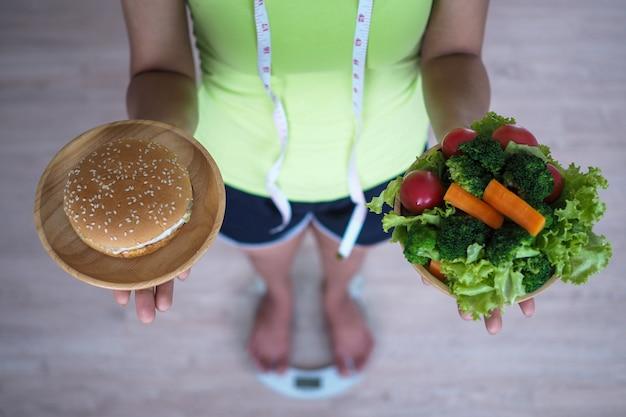 Mujer que pesa y que sostiene el plato de verduras con la hamburguesa. comida