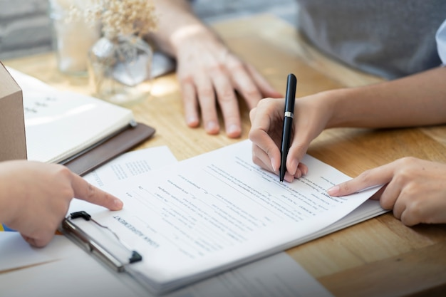 Mujer que pone contrato de préstamo de documento de firma, compra de bienes inmuebles