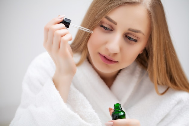 Mujer que se prepara para el trabajo que hace maquillaje de la mañana en espejo del baño en casa.