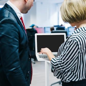 Mujer que presenta la computadora portátil al hombre en la oficina