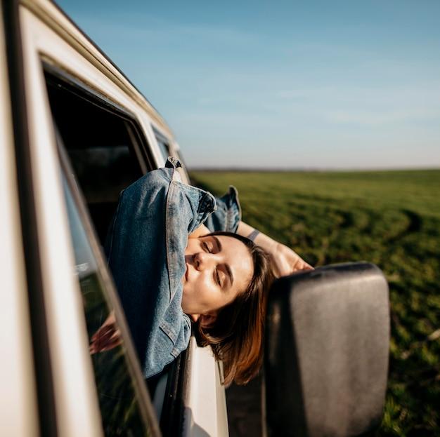 Mujer que se queda con la cabeza fuera de una camioneta