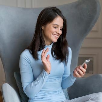 Mujer que se queda en su cama mientras tiene una videollamada en su teléfono inteligente