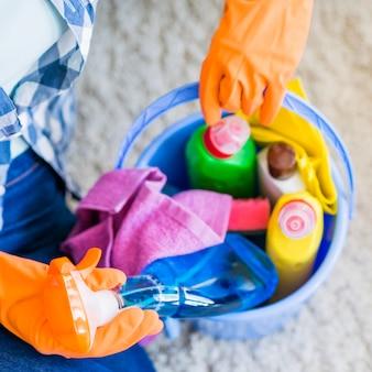 Mujer que quita la botella de spray limpiador del cubo azul