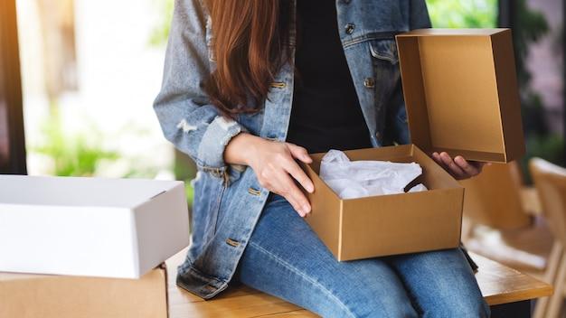 Una mujer que recibe y abre un paquete postal en casa para la entrega y el concepto de compra en línea