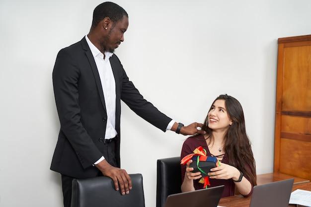 Mujer que recibe un hermoso regalo de su colega masculino mientras trabajaba en la oficina, concepto de relaciones