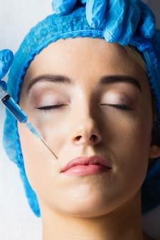 Mujer que recibe la inyección de botox en sus labios