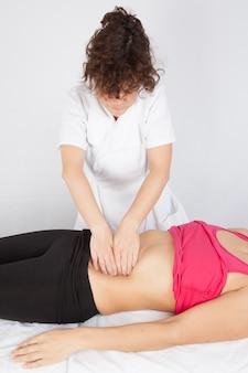 Mujer que recibe masaje abs en el salón de spa