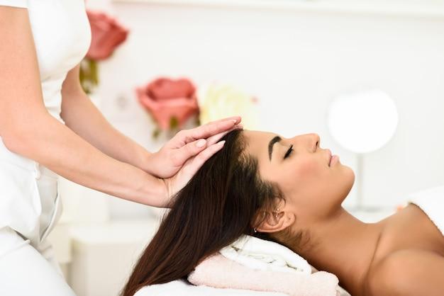 Mujer que recibe el masaje de cabeza en el centro de spa spa.