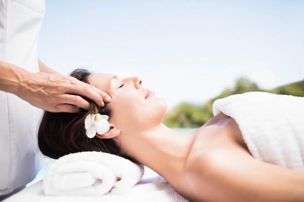 Mujer que recibe un masaje de cabeza de masajista en un spa