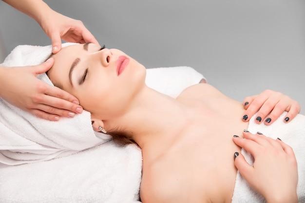 Mujer que recibe el masaje de la cabeza en el spa